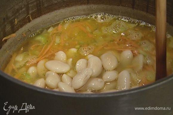 Добавить фасоль вместе с бульоном и нарезанный порей. Варить до готовности порея, около 10 минут.