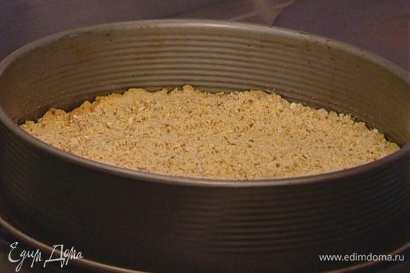 Миндаль измельчить в блендере и присыпать им пропеченное тесто.