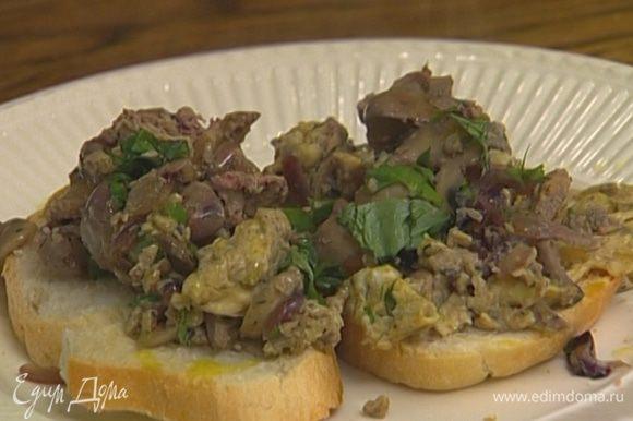 Зеленый лук и базилик мелко нарезать, добавить к омлету, порубить все вместе ножом и выложить на тосты.