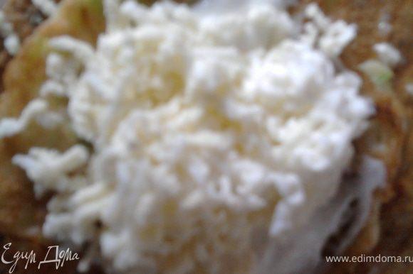 Отварить два яйца, натереть на мелкой терке. Майонез (у меня домашний) смешать с давленым чесноком и мелко нарубленым укропом. На мелкой терке также натереть плавленый сырок (или протереть творог). Берем оладушек и намазываем его майонезно-чесночной смесью, а сверху кладем чайную ложечку натертых яиц.