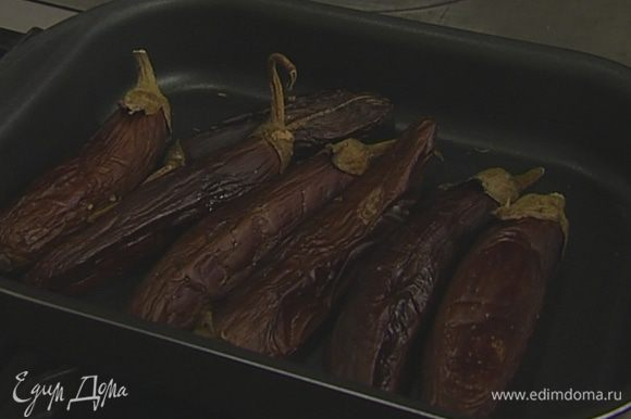 Каждый баклажан проткнуть вилкой в нескольких местах (чем больше будет дырочек, тем лучше). Уложить баклажаны на противень и запекать в разогретой духовке 40-60 минут, в зависимости их от размера. Запеченные баклажаны опустить в холодную подсоленную воду, очистить от кожицы и порубить на мелкие кусочки.
