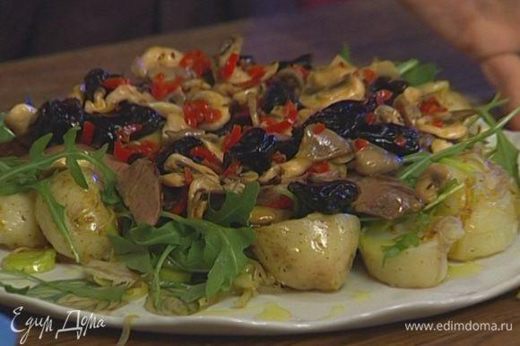 Выложить на большое блюдо картофель с луком, присыпать руколой, положить кусочки печени. Сверху разложить чернослив с грибами и сбрызнуть оливковым маслом.