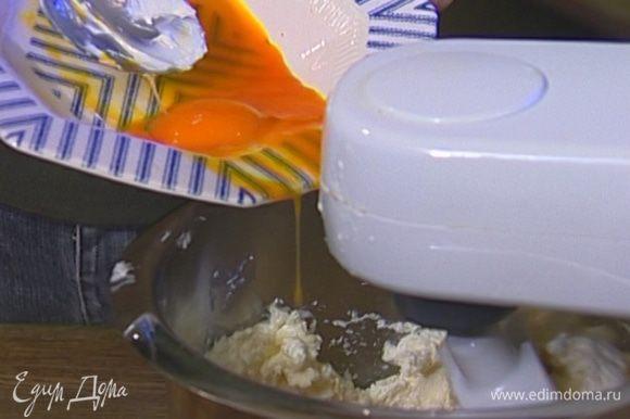 Приготовить крем: сливочный сыр размягчить в миксере на небольшой скорости, затем добавить яичные желтки и цедру лимона.