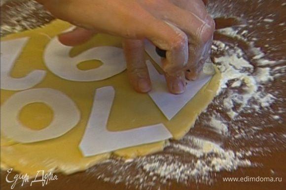 Раскатать тесто в пласт толщиной примерно 5 мм и вырезать из него печенье с помощью рюмки или специальных формочек (интересный вариант — сделать из бумаги цифры и, положив их на тесто, вырезать ножом печенье в форме цифр).