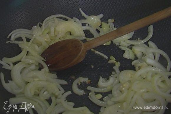 Разогреть в сковороде-вок кунжутное масло и обжарить лук и чеснок.