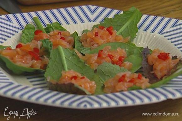 Листья салата выложить на тарелку. На каждый лист положить по столовой ложке семги, сверху по щепотке рубленого чили, лайма и орехов, полить небольшим количеством соуса, присыпать кинзой.