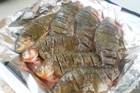 Рыбу почистить, выпотрошить, сделать надрезы. Сбрызнуть соком лимона. Посолить. Приправить специями. Запекать в духовке при 180 С в течение 40-60 минут.