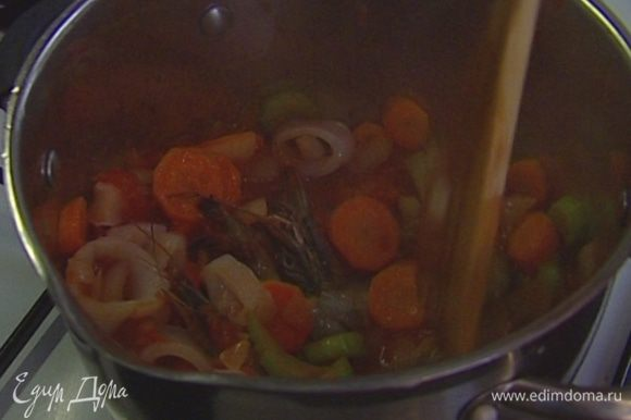 Отправить в кастрюлю с овощами половину консервированных помидоров вместе с соком и все прогреть, затем добавить креветок и кальмаров и тушить еще несколько минут.