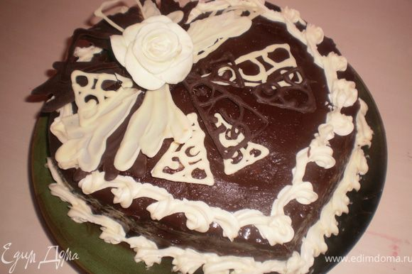 Остывший торт украшаем шоколадными завитушками, мастичной розой, делаем из крема бордюр.