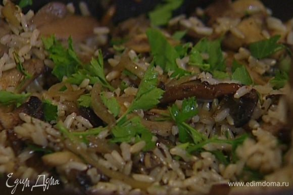 Выложить в сковороду отваренный рис, перемешать, затем добавить рубленую петрушку.