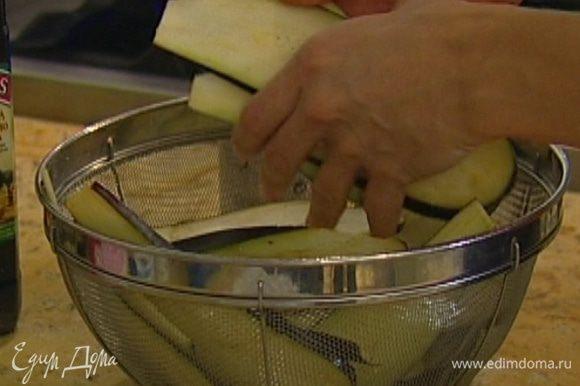 Баклажаны нарезать вдоль пластинами, выложить в дуршлаг, посыпать солью, перемешать и оставить на 20–30 минут, затем промыть холодной водой и просушить бумажным полотенцем.
