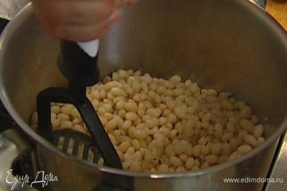 Жидкость слить в отдельную посуду, а фасоль слегка размять толкушкой, не превращая в пюре.