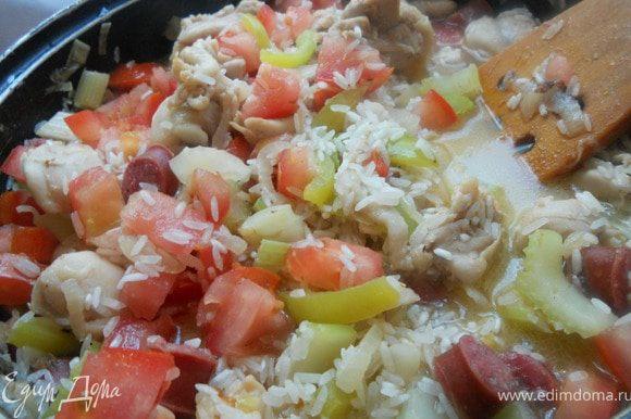 Вернуть к луку, перцу и сельдерею курицу и колбаски, засыпать рис, добавить измельченные томаты. Налить 300-400 мл. воды (можно заменить бульоном), довести до кипения, огонь убавить и далее готовить, регулярно помешивая и добавляя понемногу воды, практически до готовности риса ***лично я предпочитаю состояние аль-денте***.