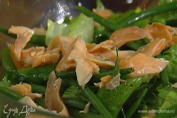Готовую рыбу разломить на небольшие кусочки и добавить в салат, затем еще раз все слегка перемешать.