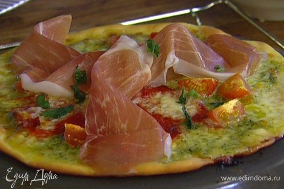 Выпекать в разогретой духовке 10–15 минут, затем пиццу вынуть, разложить сверху кусочки пармской ветчины и присыпать оставшимся базиликом.