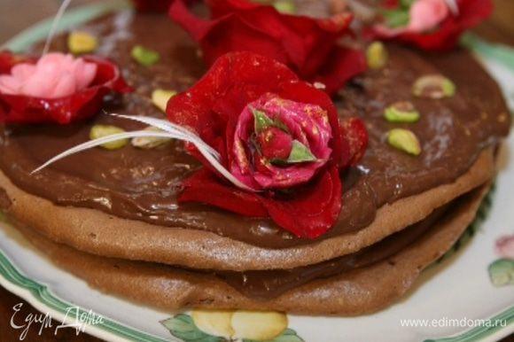 Смазать остывшие меренги шоколадным кремом, уложить одну на другую и украсить сверху, например, живыми красными розами, и присыпать фисташками.