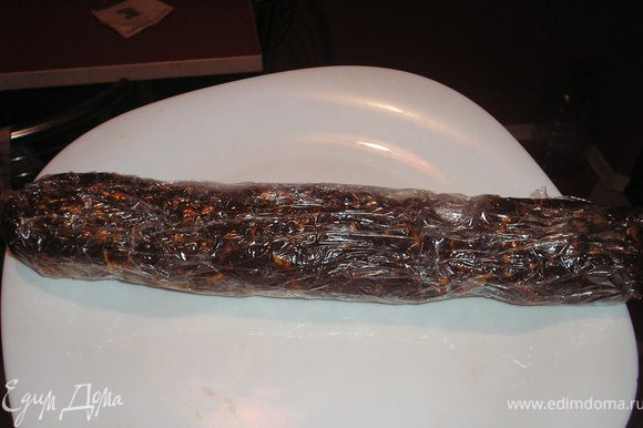 Добавить печенье, хорошо вымесить, сформировать на пишевой пленке полено, придать форму колбасы. Обернуть пленкой и поставить на несколько часов в холодильник.