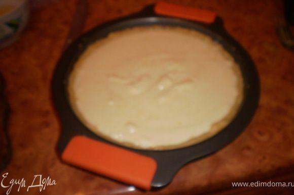 В форму выложить тесто, распределить, сформировать бортики. Вылить крем.