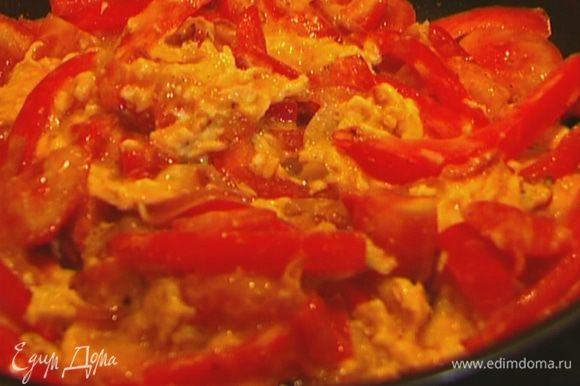 Яйца слегка взбить вилкой, посолить, поперчить и влить в сковороду с овощами. Помешивая, обжаривать буквально минуту, затем разложить по тарелкам.