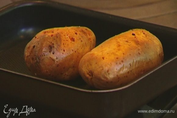 Картофель наколоть вилкой со всех сторон, выложить на противень и отправить в разогретую духовку на 45−60 минут.