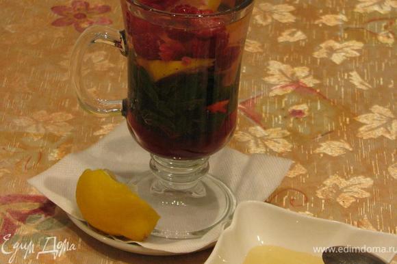Положить мяту в бокал или чашку. Малину слегка подавить, чтобы она пустила сок, добавить к мяте вместе с двумя кусочками лимона. Залить кипятком. Дать настояться несколько минут. Добавить мед по вкусу.