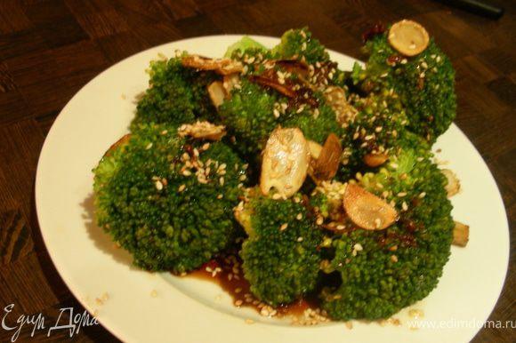 Подаем брокколи горячей, полив заправкой и посыпав чесночными чипсами и кунжутом. Приятного аппетита!