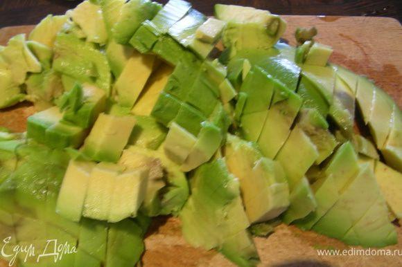 Авокадо разрезаем вдоль напополам, удаляем косточку, аккуратно вынимаем мякоть, сохраняя невредимыми половинки. Нарезаем авокадо помельче.
