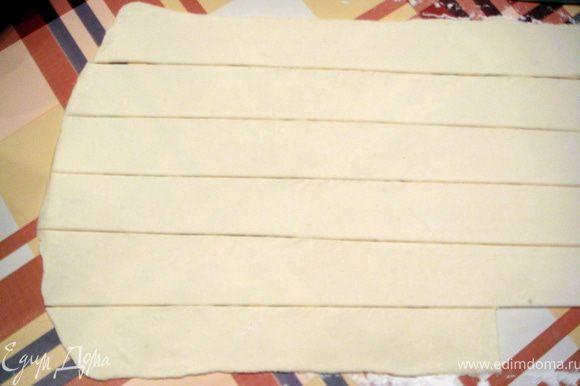 Тесто разморозить по инструкции и раскатать в одном направлении до толщины 0,5 см. Разрезать на полоски шириной 2 см и ддлиной 20 см.