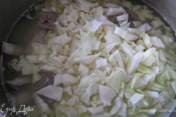 Тем временем нашинковать капусту, добавить в кастрюлю. Варить 10-15 минут.
