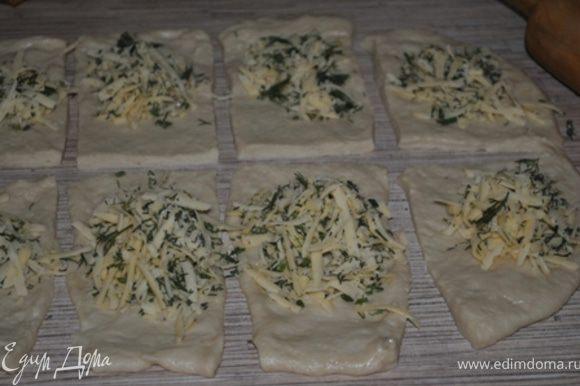 Готовое тесто разделить на 2 части. Раскатать в тонкий пласт, каждый разрезать на 10 прямоугольников. Смазать маслом, в центр каждого положить начинку.