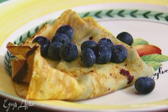 В готовые блины завернуть черничную начинку, украсить ягодами черники.