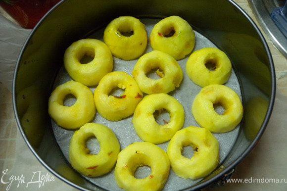 Яблоки почистить от кожуры и сердцевины. Порезать пополам и уложить срезами на дно формы. В форму предварительно застрелить бумагу и дно и стенки смазать растительным маслом.
