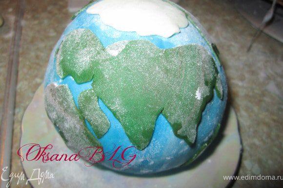 """Из зеленой мастики вырезать """"континенты"""", прикрепить на шар, смочив немного водой."""