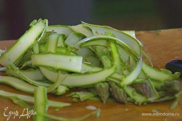 Спаржу, удалив грубые черенки, нарезать овощечисткой длинными тонкими полосками.