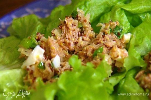На хлеб положить листья салата, на них выложить начинку из тунца.