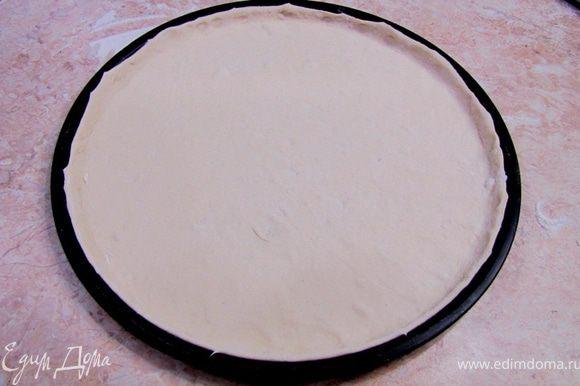 Положите тесто в кастрюлю и накройте мокрым полотенцем на пол часа. Достаньте тесто и раскатайте его. Я использовал специальную форму для пиццы. Уложите тесто в форму, предварительно посыпав ее манной крупой или выложив его на бумагу для запекания, предварительно смазав бумагу сливочным маслом. Сформируйте из теста бортики, так как начинки в данной пицце довольно много. Отставьте форму с тестом в сторону на 20 минут.