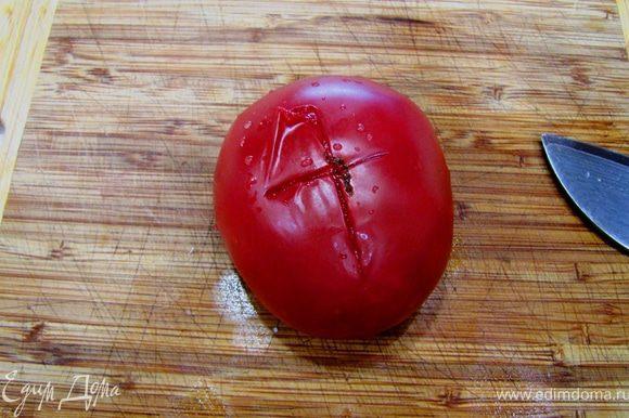 Достаньте помидоры из кипятка и обдайте их холодной водой. Разрежьте кожицу крест на крест.