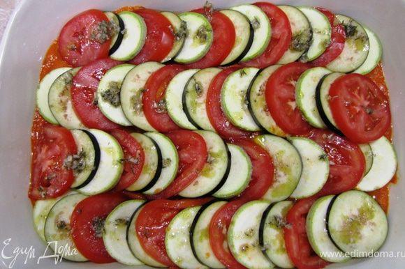 Нарежьте овощи кольцами одинаковой толщины - около 3 миллиметров. Выложите овощи поверх соуса под уклоном, как показано на фотографии, чередуя все овощи. Еще раз повторюсь, лучшее сочетание: помидор, цукини, желтый кабачок, баклажан. У меня не было ни цукини, ни желтого кабачка и я воспользовался только обычным кабачком. Полейте заправкой сверху овощи.