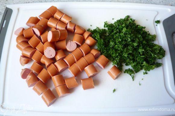 Нарезать сосиски кусочками, петрушку порубить.