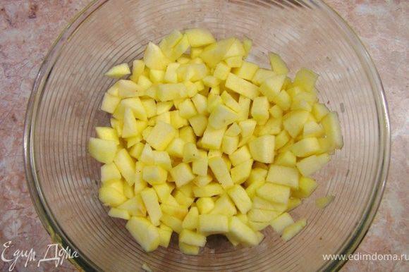 Очистите яблоки и порежьте их на небольшие кубики (можно яблоки не чистить, а только вырезать сердцевину). Сложите яблоки в емкость и сразу полейте 2 столовыми ложками лимонного сока, чтобы яблоки не потемнели. Перемешайте яблоки.