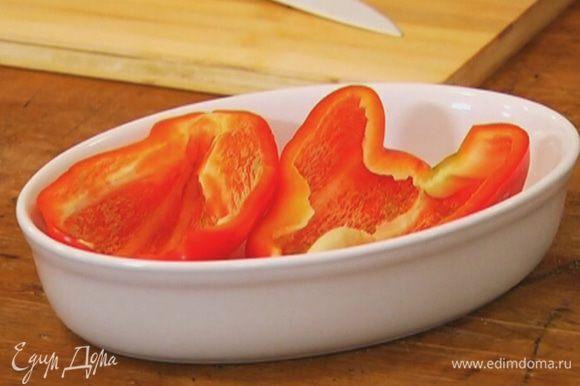 Перец разрезать вдоль пополам и, удалив плодоножку и перепонки, поместить в небольшую форму для выпечки.
