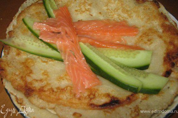 На блинчик нанести тонкий слой майонеза, затем тёртого сыра, затем начинку, н-р огурчик и красную рыбку тонкими полосками