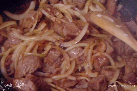 Лук нарезать полукольцами, чеснок измельчить и добавить все в мясо, обжарить до золотистого цвета.