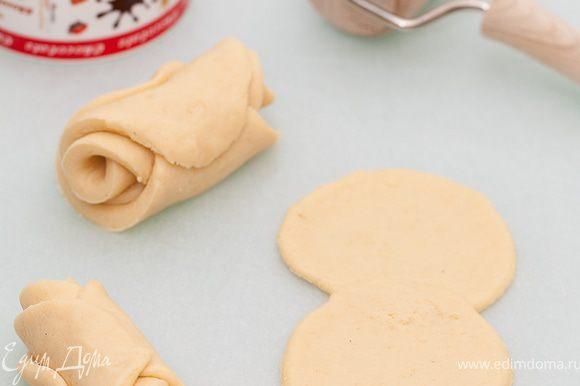 Раскатываем тесто и вырезаем из него кружочки с помощью чашки.