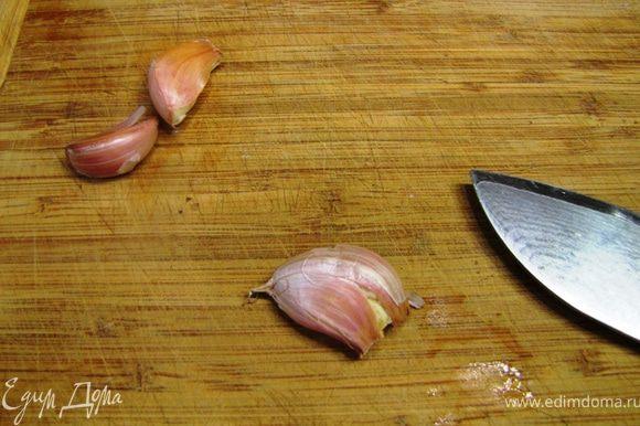 Возьмите зубчики чеснока и плоской стороной ножа раздавите их. Теперь будет легко снять кожицу.