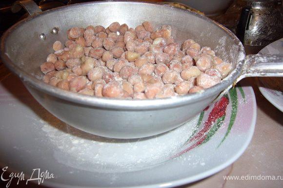Посыпь орешки сахарной пудрой и кокосовой стружкой.