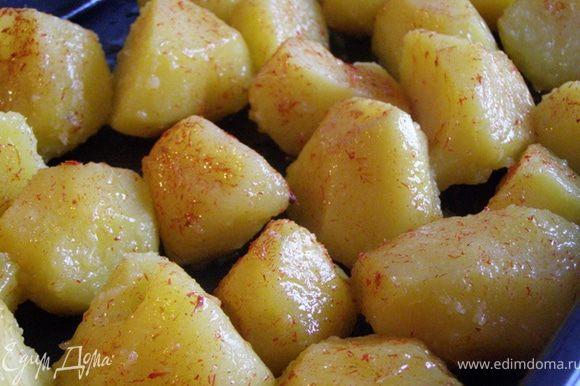 На горячий противень выложим отварной картофель, встряхнем противень, чтобы смешать картофель с маслом. С помощью кисти смажем картофелины шафранным маслом.
