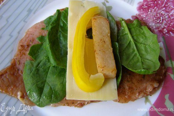 На подготовленное филе разложить по 4-5 листиков шпината, на расстоянии 3 см от края положить пластик сыра, а на него полоски перца и груши.