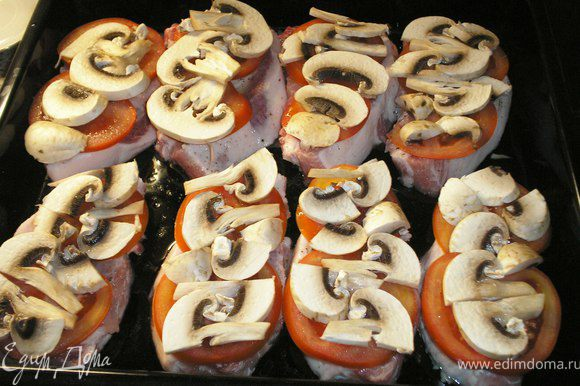 Шампиньоны порезать кусочками и выложить на мясо поверх помидоров.