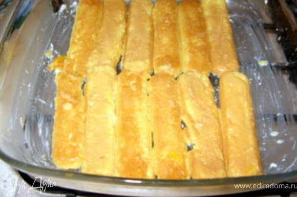 Смазать форму для выпечки сливочным маслом и выложить первый слой савойярди.